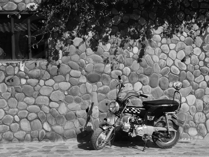 Motorbike stone wall black and white Peru photo