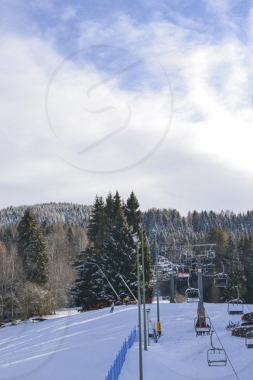 Ski resort Nevegal slope people on the ski lift skiers on the piste among white snow pine tree. photo