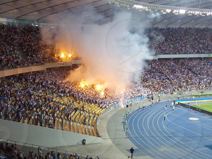 person in olympic stadium with white smoke photo