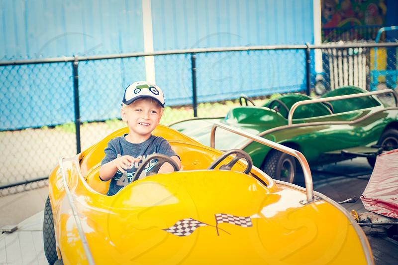 boy youth child amusement park ride fun summer fair yellow car race car around circle carousel green blue cap hat happy rides checker flags photo