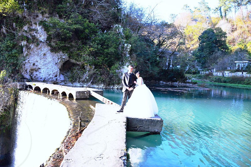man in black coat beside woman in white gown standing in white concrete stand near body of water during daytime photo
