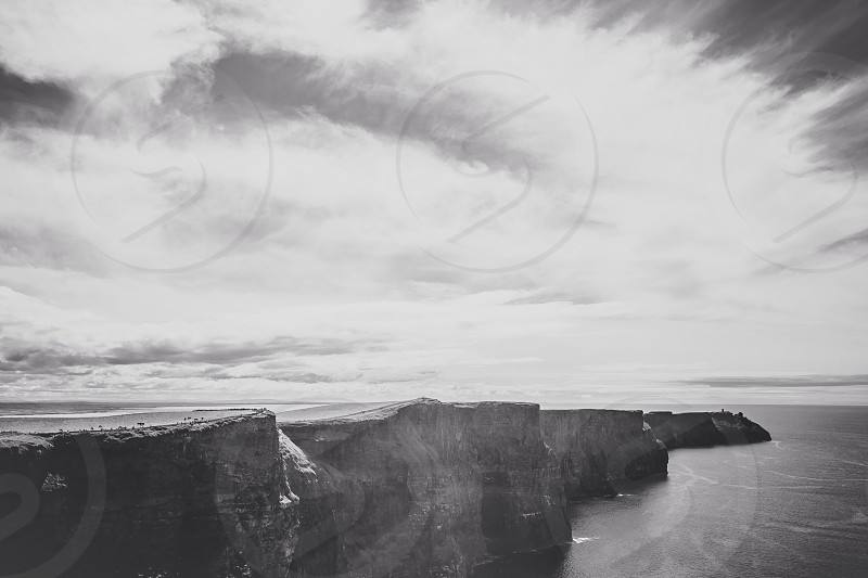 greyscale photography of cliff beside body of water photo