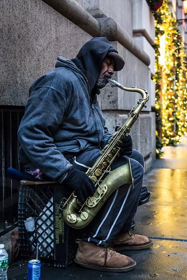 Street performer plays the saxophone on a Manhattan New York sidewalk in winter. photo
