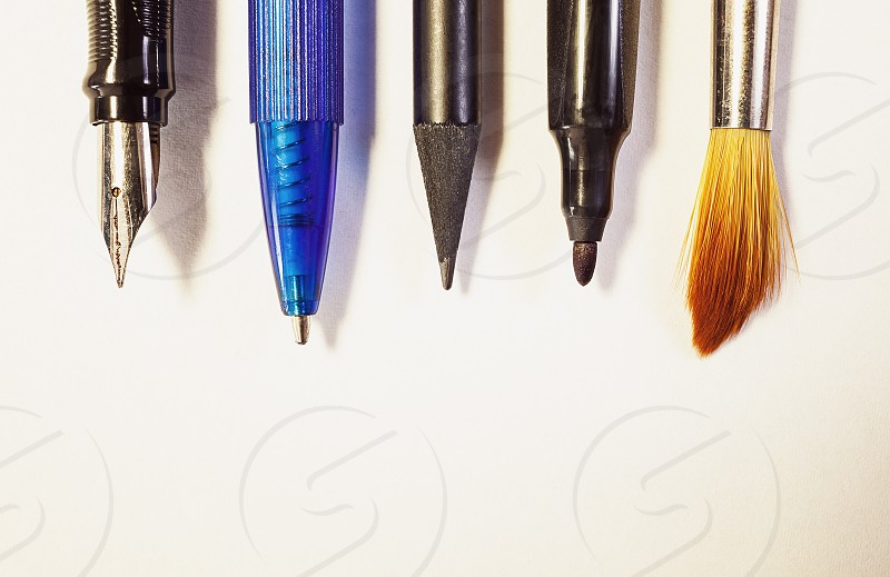 Various tools for writing or painting conceptual composition on white paper.  photo