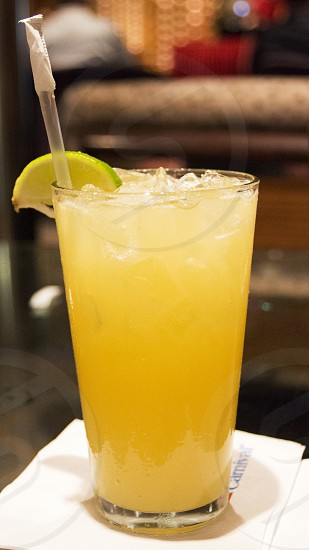 Yellow alcoholic beverage with lime slice photo