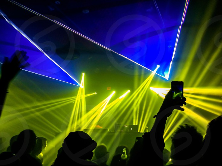 A mobile photographer captures the laser light show during an intimate performance by the DJ Pretty Lights at the Sonos Studio in West Hollywood CA.  photo