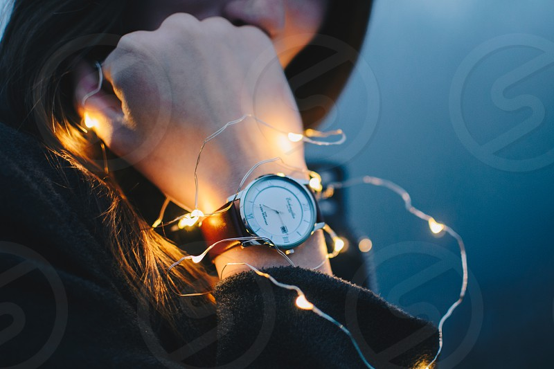 Woman wearing a watch wrapped in fairy lights. photo