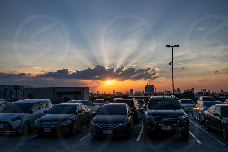 The sun is setting on twilight dramatic sky over cars on top roof carpark in Bangkok. Thailand. 27/10/18 photo