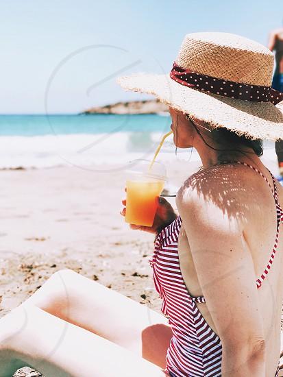 Girl woman straw hat summer summertime summer vacation drinking orange juice drinking juice beach beach portrait beach vacation beach scene fashionista seascape photo