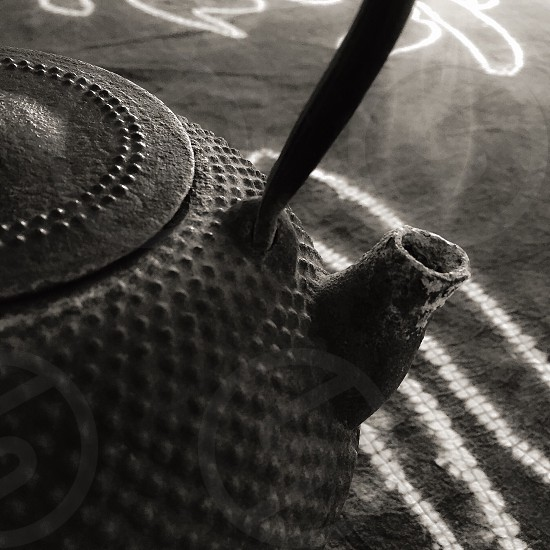 black textured metal teapot steaming in black and white photo