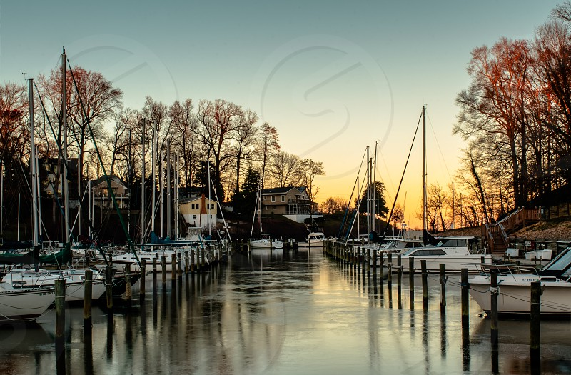 flags pond harbor boats sunset landscape red orange blue gold ice winter view lake water photo