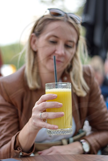 Portrait of the mature woman sitting in the restaurant drinking juice photo