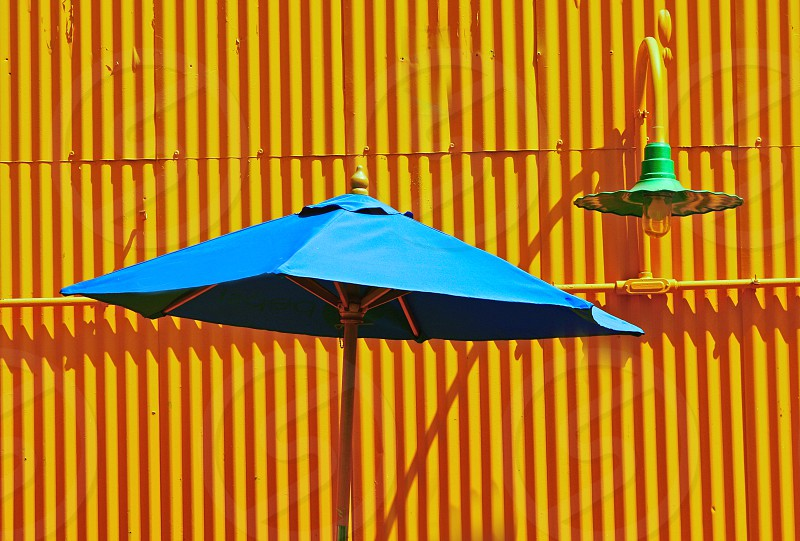 Patio at theme park with blue umbrella and yellow metal wall. photo