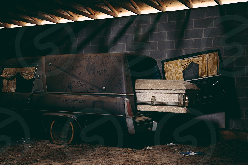 black station wagon with brown casket coming out of rear photo