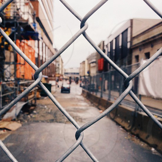 beige and orange buildings along the road behind cyclone fence in shallow focus lens photo