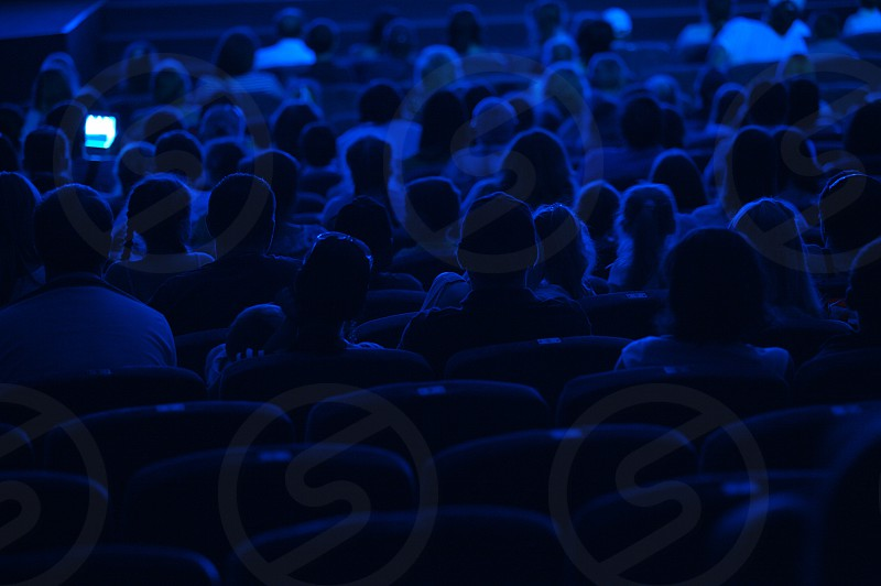 Audience in the cinema. Silhouette shot from back in blue light. photo