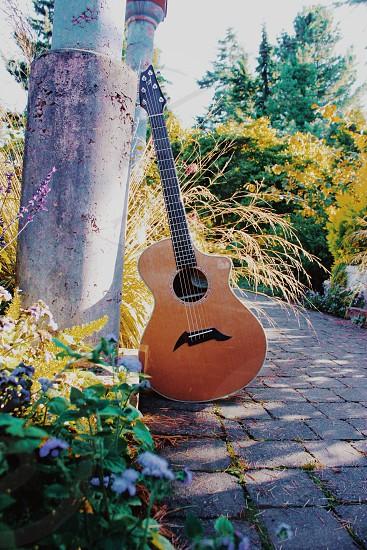 acoustic guitar against pole photo