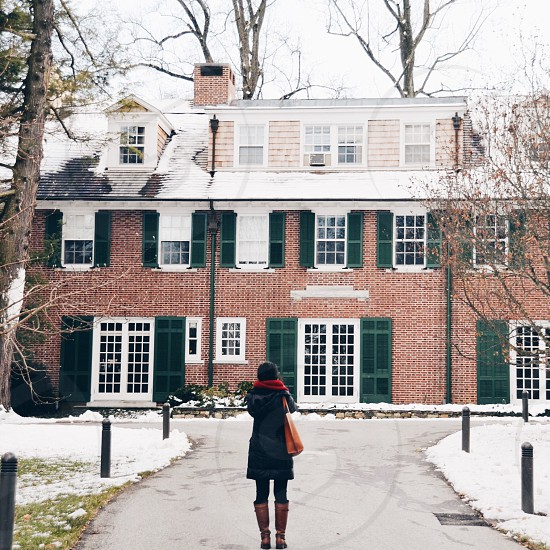 girl standing n front of a brick house with green shutters photo
