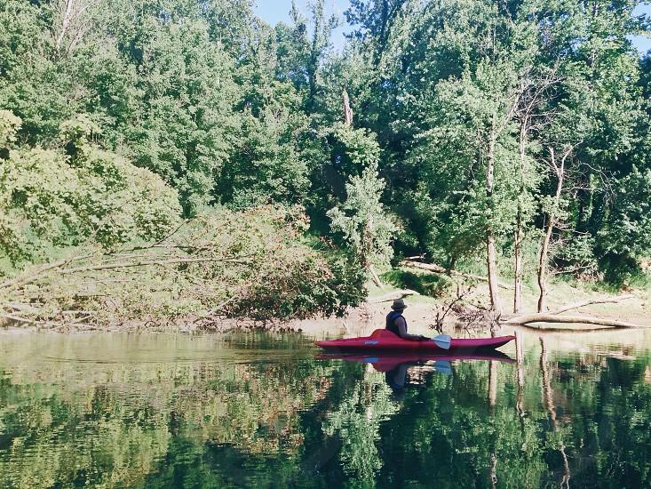 person wearing round hat riding kayak on water during daytime photo