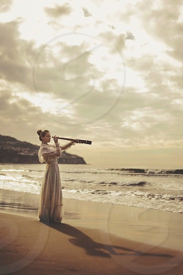 woman looking at a scope on seashore photo photo