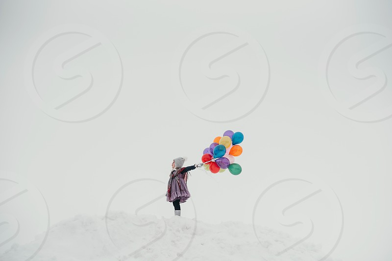 Little girl flying colorful balloons on top of a snow pile. photo