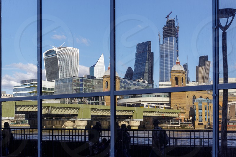 LONDON UK - MARCH 11 : City skyline reflected in a building on the south bank of the River Thames in London on March 11 2019. Unidentified people photo