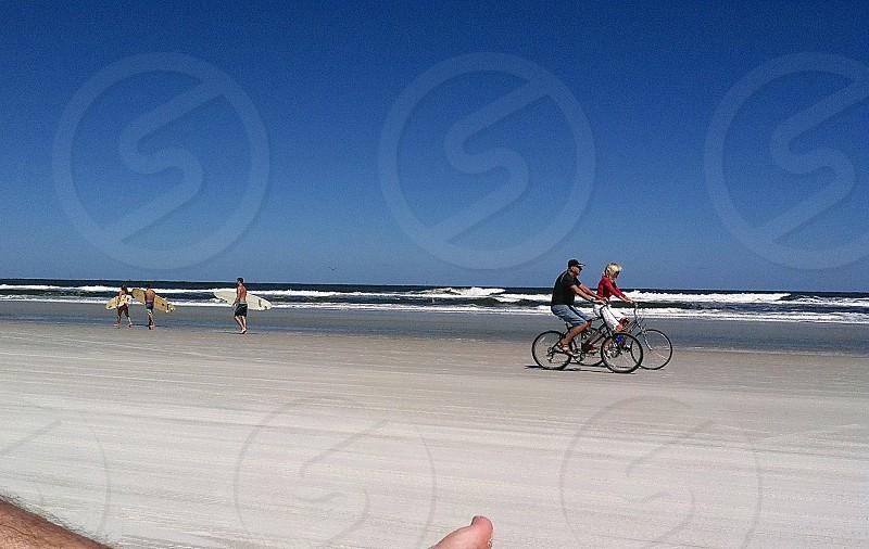 Florida Beach Surfers Couple Riding Bikes On The Beach photo