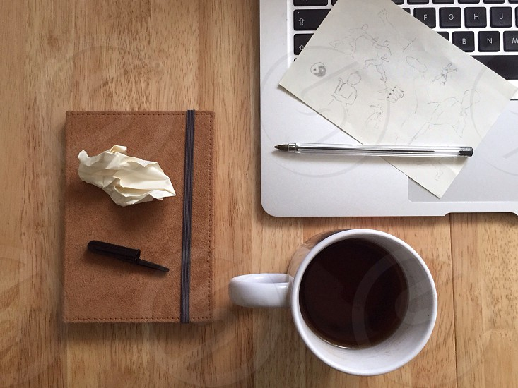 white ceramic mug with coffee beside macbook photo