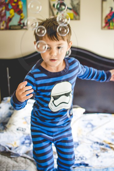 Boy Playing with bubbles in pajamas photo