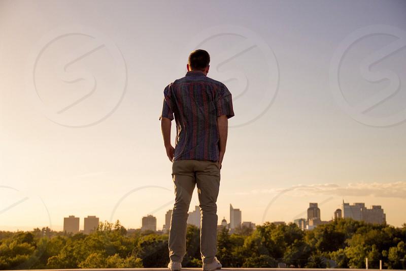 man in beige skinny jeans overlooking city building photo