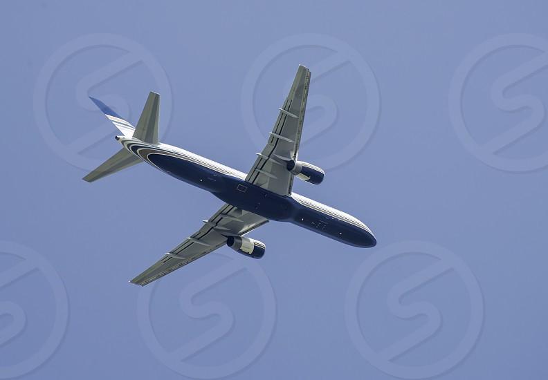 Flying white plane on blue sky background photo
