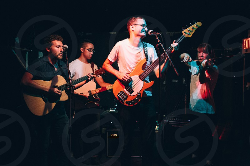 man wearing white t-shirt playing guitar with band mates on stage photo