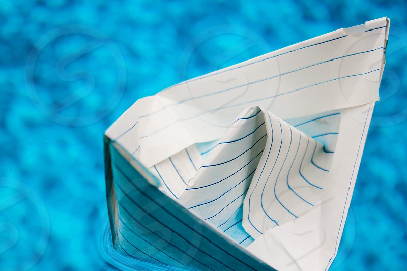 Paper boat floating on blue water. photo