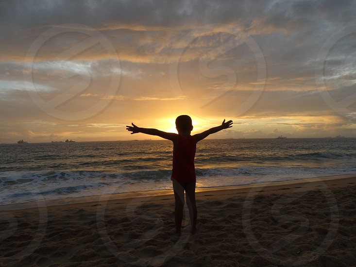 A kid in a beach at the sunrises. Itapoã Brazil. photo