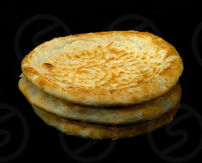 original fresh uzbek bread isolated over black background photo