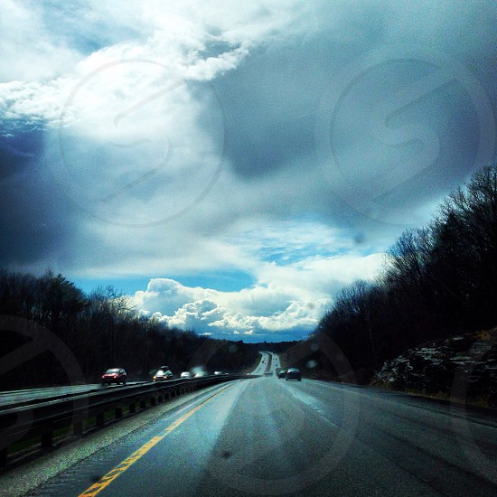 white cumulus clouds over black asphalt road photo
