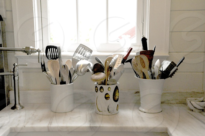 Kitchen utensils on counter by window all white photo