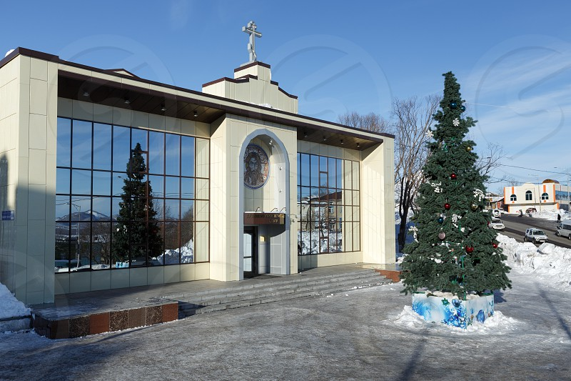 PETROPAVLOVSK CITY KAMCHATKA RUSSIA - JAN 6 2018: Diocesan Spiritual and Enlightenment Center of Petropavlovsk Kamchatka Diocese of Russian Orthodox Church and Christmas tree in front of building photo