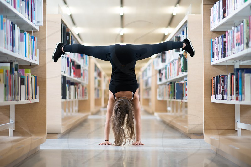 Young girl does a handstand in a library photo