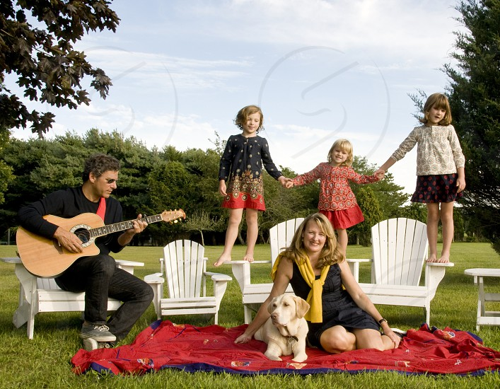 man plays guitar while sitting on adirondack with woman sitting on blanket and 3 children standing on adirondacks photo