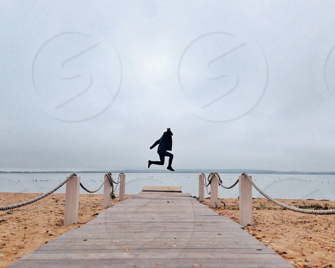 man in black jacket jumping high by the seashore during daytime photo