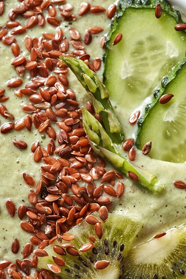 Vegetarian food smoothies from green organic vegetables with flax seeds in a white bowl macro natural green background. Top view. photo
