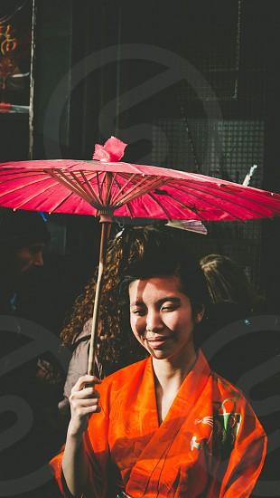 woman holding pink umbrella taking selfie photo