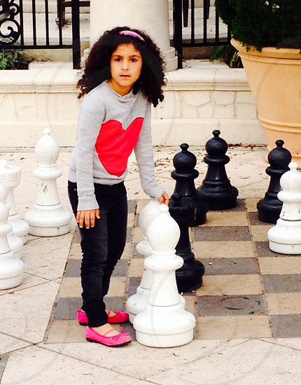 girl in gray heart printed crew-neck sweater and black pants holding white bishop chess piece statuette during daytime photo