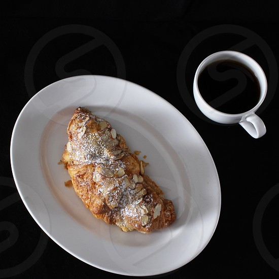Almond croissant and coffee for breakfast - Top view photo