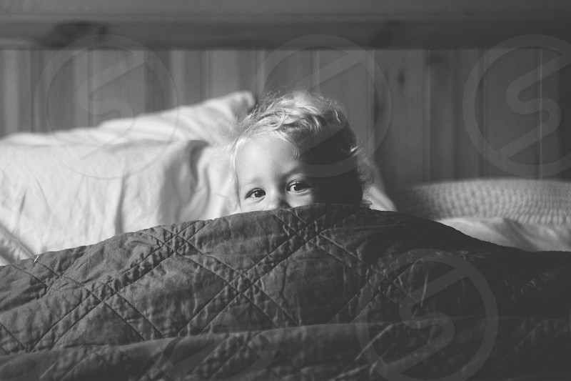 grayscale photography girl in bed covered by black quilt mattress photo