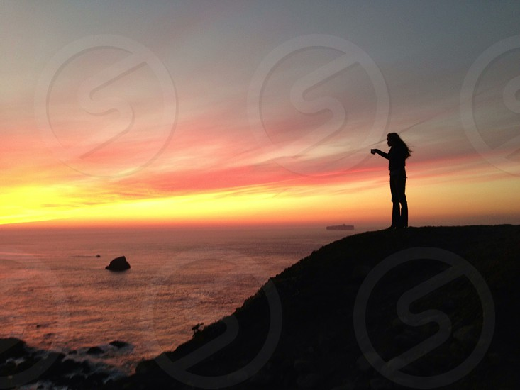 person on a hill fronting a sea photo