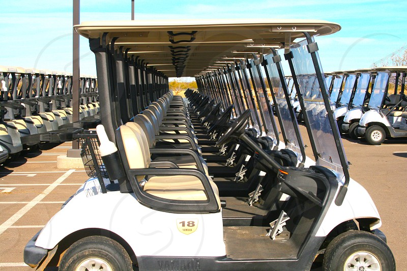 white golf carts parked on parking lot photo
