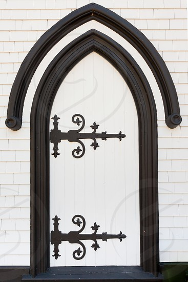 Black and white wooden door portal entrance doorway entry with artistic wrought iron hinges painted black photo