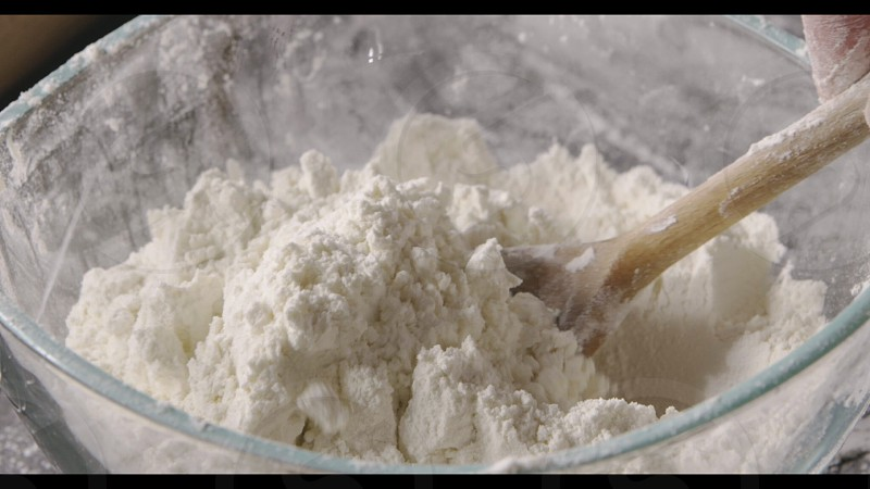 Close up process of handmade dough from flour. Girl's hand is pouring a white flour in a glass bowl . Close up slow motion Full HD video 240fps 1080p. Process preparing of pastry. photo